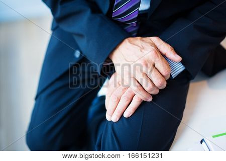 Closeup hands of businessman's hands in his lap.