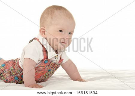 Cute baby boy crawling on blanket on a white background