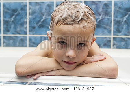 Adorable baby boy with shampoo soap suds on hair taking bath. Closeup portrait of smiling kid health care and hygiene concept as logo. Isolated on white and blue background with clipping path.