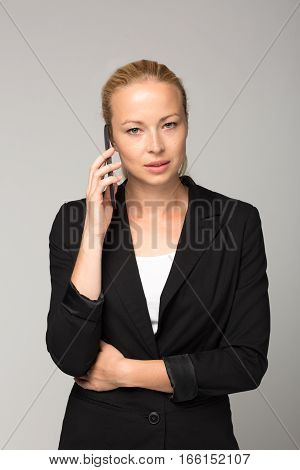 Beautiful young caucasian businesswoman wearing black business attire talking on mobile phone. Studio portrait shot on gray background.