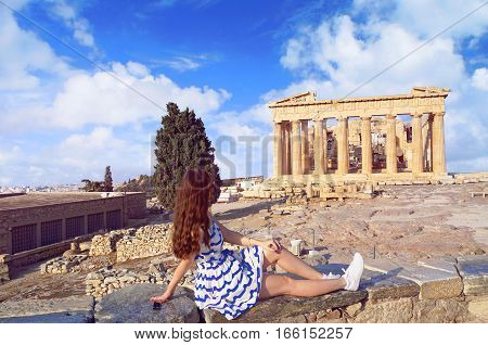 Tourist girl dressed in Greece flag colors looking at Parthenon on the Acropolis on summer sunny day in Athens.