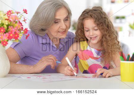 grandmother helping her granddaughter doing homework, educational concept