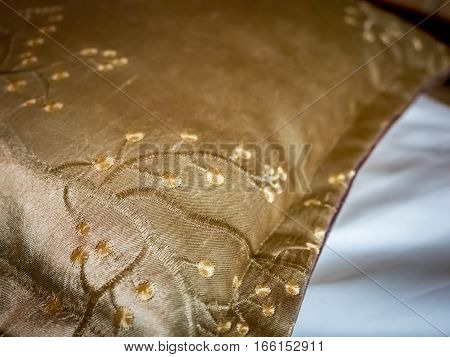 Golden color cushion cover with cherry blossom embroidery motif. High resolution, shallow depth-of-field image showing detailed stitching pattern.