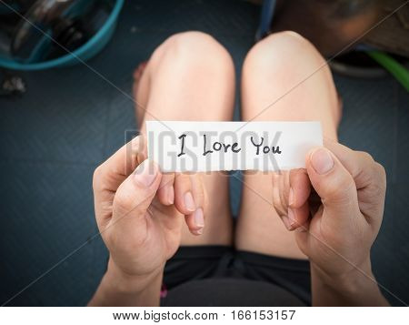 Woman's hand holding a paper with the message I received from her lover on Valentine's Day.