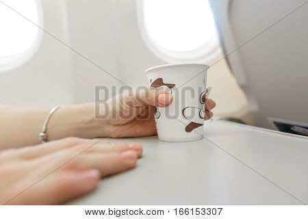 Woman  drinking coffee on airplane. Female traveler seated in passanger cabin.