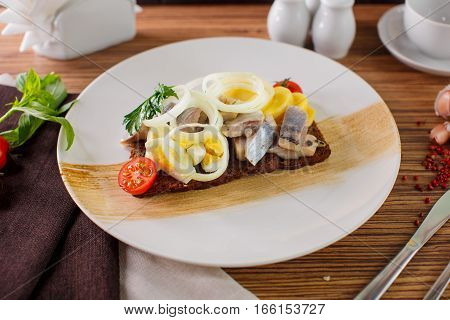 Russian menu Herring with potatoes and eggs on a white plate