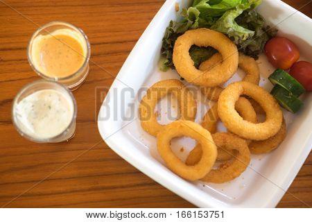 Fast food deep fried onion ring on wood table