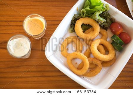 Delicious pub style onion rings in white dish