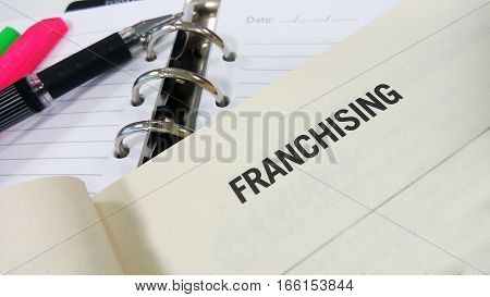 Franchising word printed on a white book