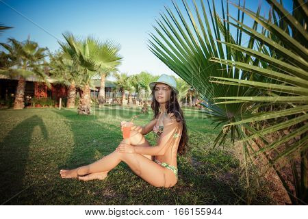 woman with cocktail relaxing under the palm trees