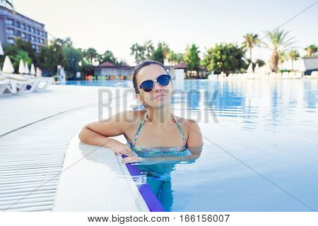 Close up portrait of a beautiful young woman in swimming pool