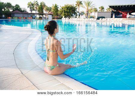 Young brunette woman splashing water in swimming pool
