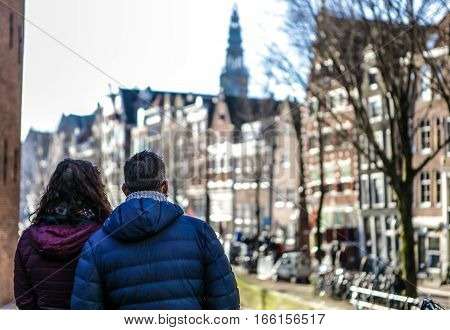 Adult couple of tourists observing beautiful Amsterdam city.