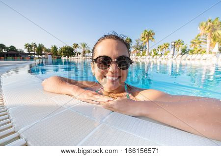 Close up portrait of a happy young woman in swimming pool
