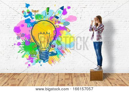 Young girl standing in room with business sketch and lamp. Idea concept