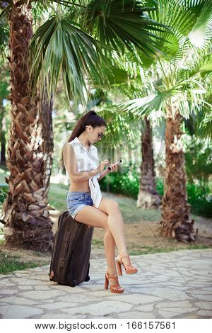 young woman in sunglasses, white shirt and shorts sitting on  suitcase with smartphone