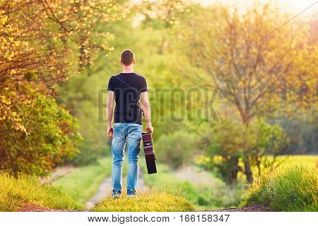Guy with guitar. Handsome young man is enjoying in springtime.