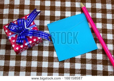 Blue Leaf For Notes With Pencil And Gift On Table, Top View. Checkered Background