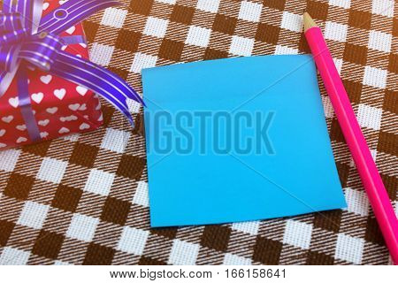 Blue Sheet Of Paper For Notes, Pencil And Gift On Table, Closeup. Checkered Background