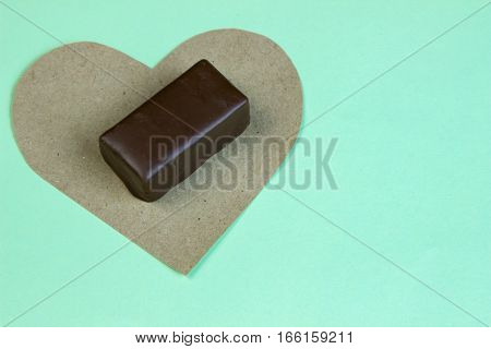 Candy Cane On A Piece Of Paper Heart With A Cup Of Coffee On Turquoise Background