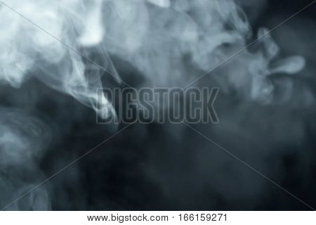 smoke slowly floating through space against black background