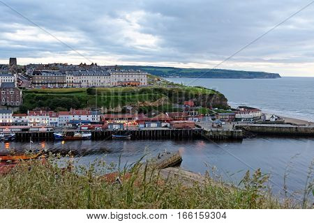 WHITBY, ENGLAND - JUNE 30, 2016: A seaside town port and civil parish at the mouth of the River Esk. Whitby has an established maritime mineral and tourist heritage.