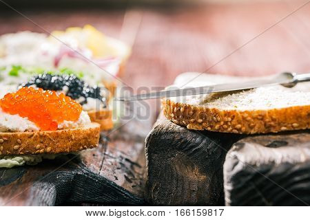 Bran bread toast and spreading knife next to sandwiches served on rustic wood board