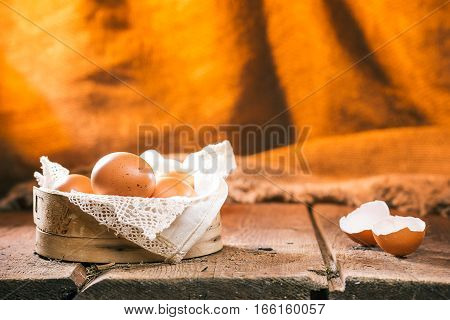 Raw eggs in a sieve on wood boards. Egg shell near them. Wood and burlap rustic background