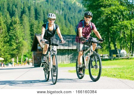 Active senior couple being active outdoors in summer.