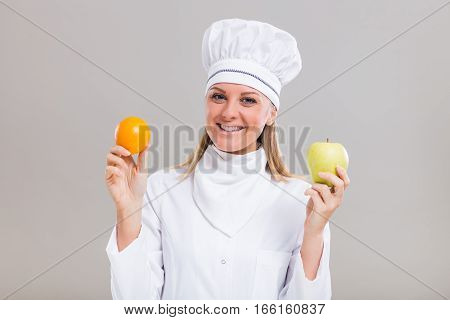 Beautiful female chef is showing fruit on gray background.