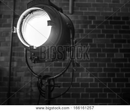 Old searchlight against brick wall close-up. Black-white photo.