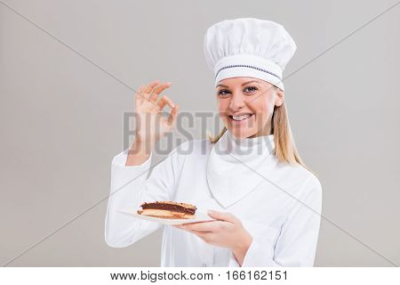 Beautiful female confectioner is showing ok sign and slice of cake on gray background.
