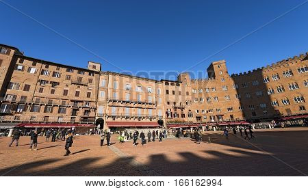 SIENA ITALY - JANUARY 5 2017: Many tourists visit the ancient and medieval Piazza del Campo (Campo square) in the downtown of Siena Toscana (Tuscany) Italy