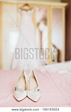 Bride's shoes for the wedding day on pink bed sheet