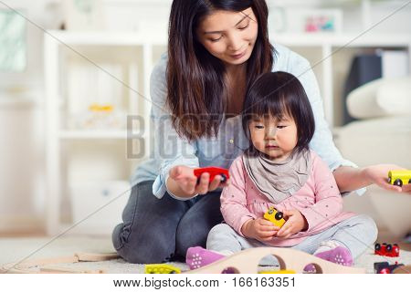 Pretty Happy Japanese Mother Play With Her Little Toddler Daughter At Home