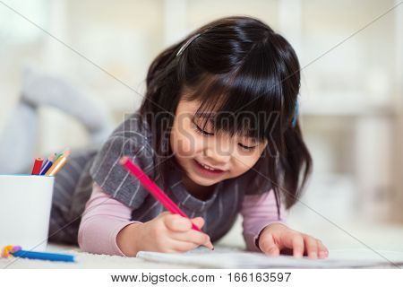 Pretty Happy Little Japanese Girl Drawing With Pencils At Home