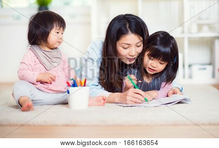 Happy Japanese Mother Play With Her Two Cute Little Daughters At Home