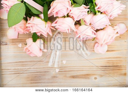 Pink blooming fresh valentines day roses on wood with two cristal champagne glasses