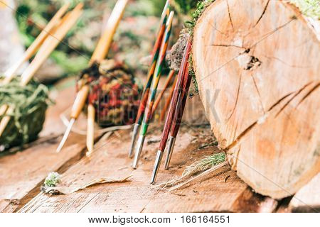 Wood needles assortment next to natural log. Concept of eco style needle shop