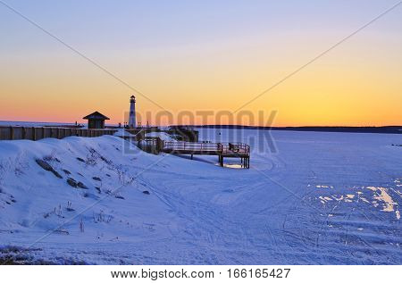 Winter Lighthouse Sunrise. Sunrise on the shores of Lake Huron with the Wawatam Lighthouse and Mackinaw Island in the background. St. Ignace, Michigan