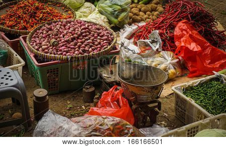 Green grocer sells vegetables, herbs and spices at traditional market in Jakarta Indonesia java