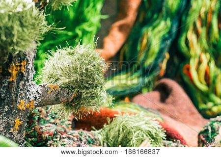 Variety of green yarns with raw wood decorations. Concept of environmental friendly yarn shop. Selective focus
