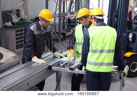 Workers in uniform in CNC machine shop with lathes