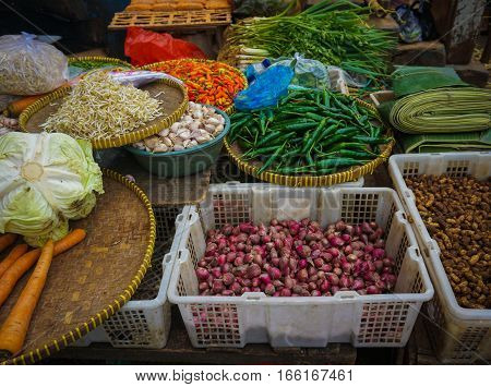 Green grocer sells various kind of vegetables, herbs and spices at traditional market in Jakarta Indonesia java