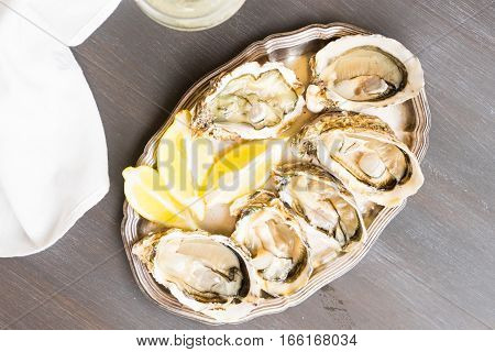 Raw oysters shells and glass of white wine, top view on wooden table