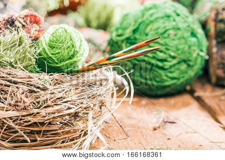 Green yarn balls and wood colorful needles in nest. Concept of eco friendly knitting goods
