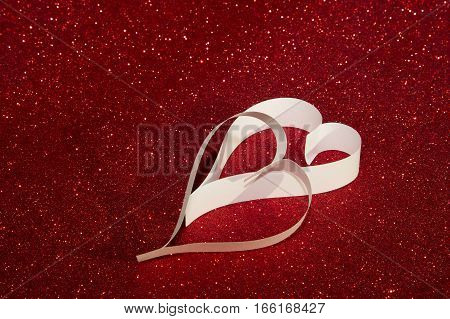 Two white hearts from paper on red shining background