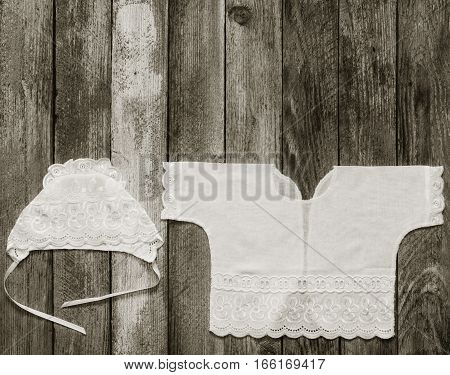 black & white photo of a cap and a shirt for a newborn on the old rustic wooden table close-up view from above. with space for text