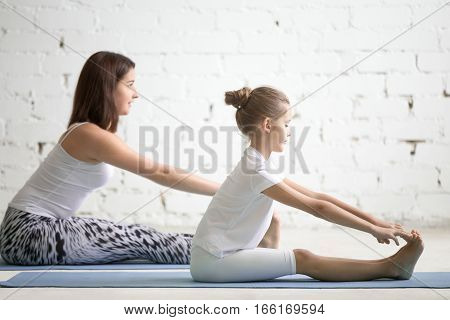 Kids yoga female teacher training a girl child, two people practicing yoga, sitting in paschimottanasana exercise, seated forward bend pose, working out wearing sportswear, indoor, white studio