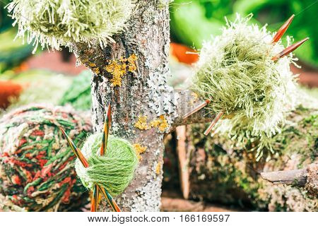 Assortment of green yarns and wooden colorful needles with raw wood decorations. Concept of eco style knitting shop. Close up